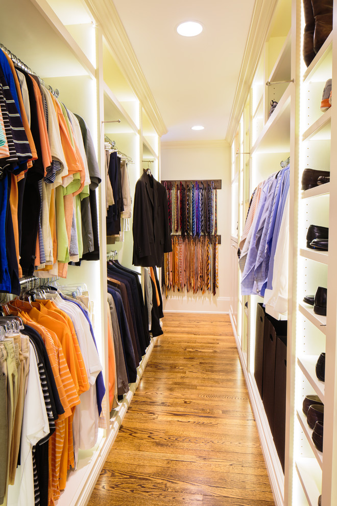 Elegant men's medium tone wood floor walk-in closet photo in Other with open cabinets and white cabinets