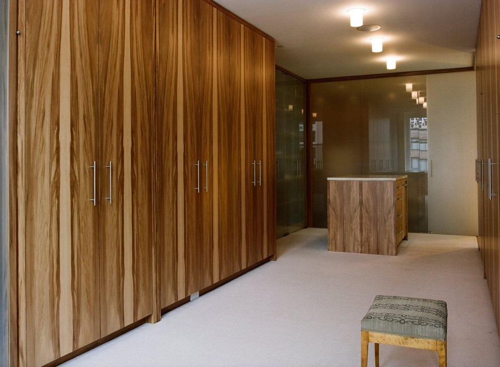 Inspiration for a contemporary gender-neutral carpeted dressing room remodel in Chicago with flat-panel cabinets and medium tone wood cabinets