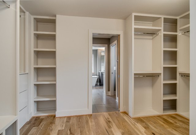 Example of a large minimalist gender-neutral light wood floor walk-in closet design in Nashville with open cabinets and white cabinets