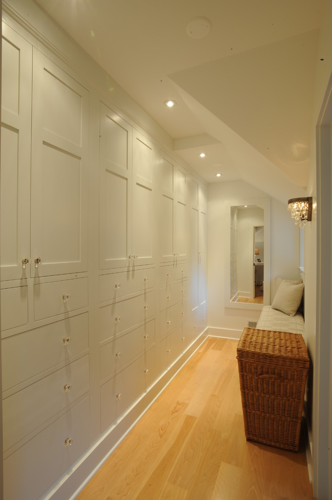 Example of a country light wood floor walk-in closet design in Cleveland with shaker cabinets and white cabinets