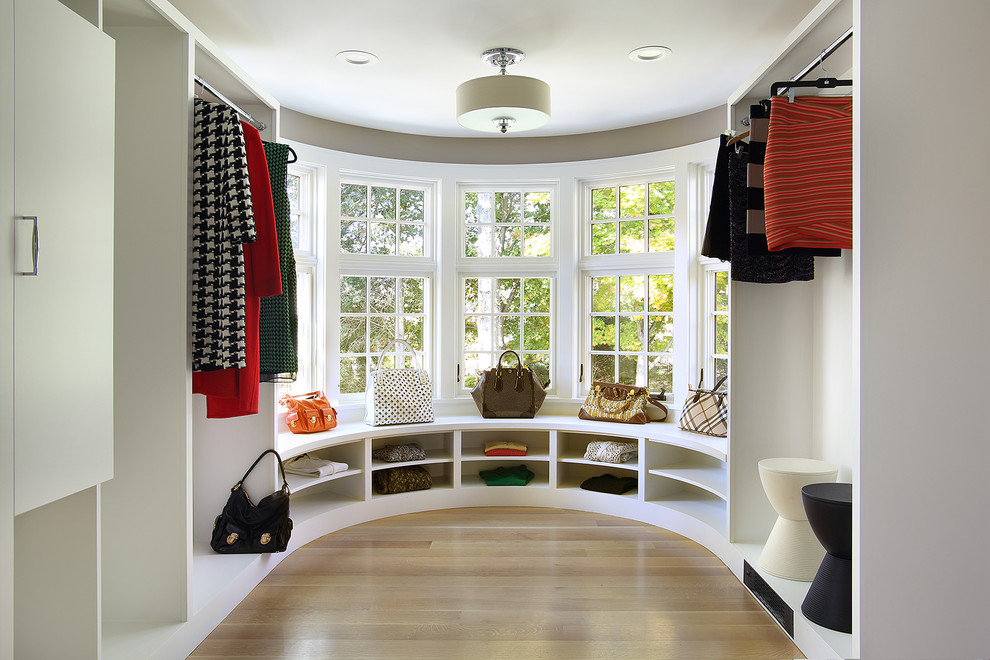 Dressing room - transitional light wood floor and beige floor dressing room idea in New York with open cabinets and white cabinets