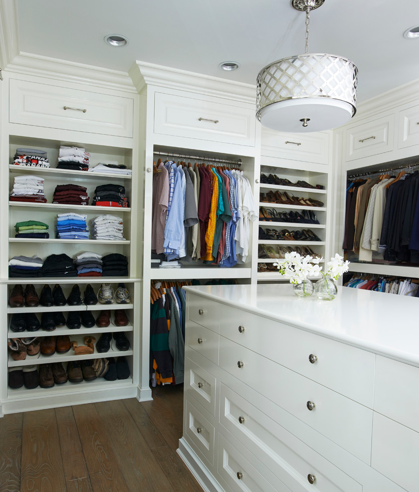 Large elegant gender-neutral dark wood floor and brown floor walk-in closet photo in New York with white cabinets and flat-panel cabinets
