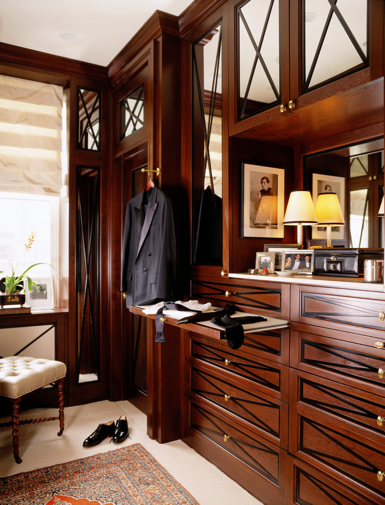 Elegant men's walk-in closet photo in Chicago with dark wood cabinets