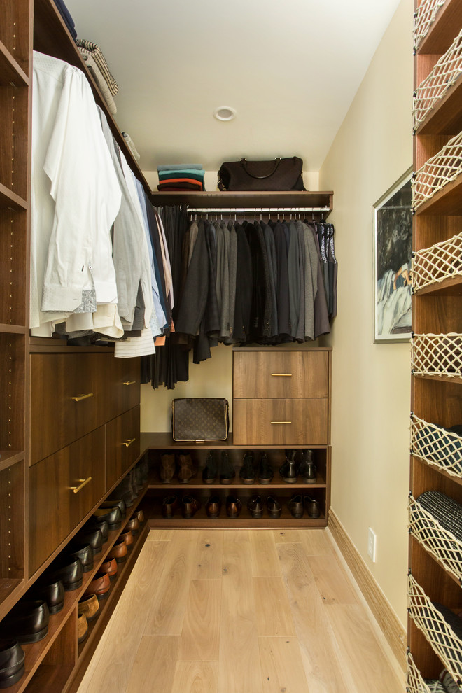 Walk-in closet - mid-sized men's light wood floor and beige floor walk-in closet idea in Los Angeles with flat-panel cabinets and dark wood cabinets