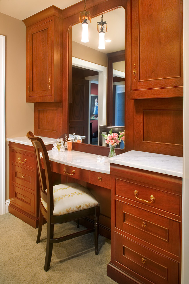 Dressing room - large traditional carpeted dressing room idea in Grand Rapids with beaded inset cabinets and medium tone wood cabinets