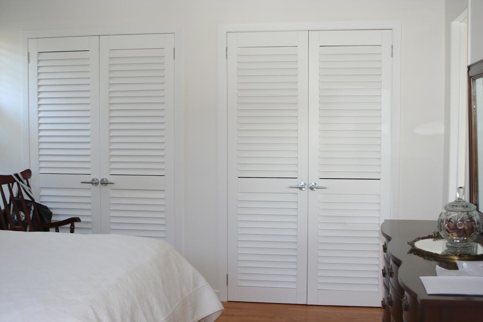 Reach-in closet - mid-sized traditional gender-neutral medium tone wood floor and brown floor reach-in closet idea in Toronto with louvered cabinets and white cabinets