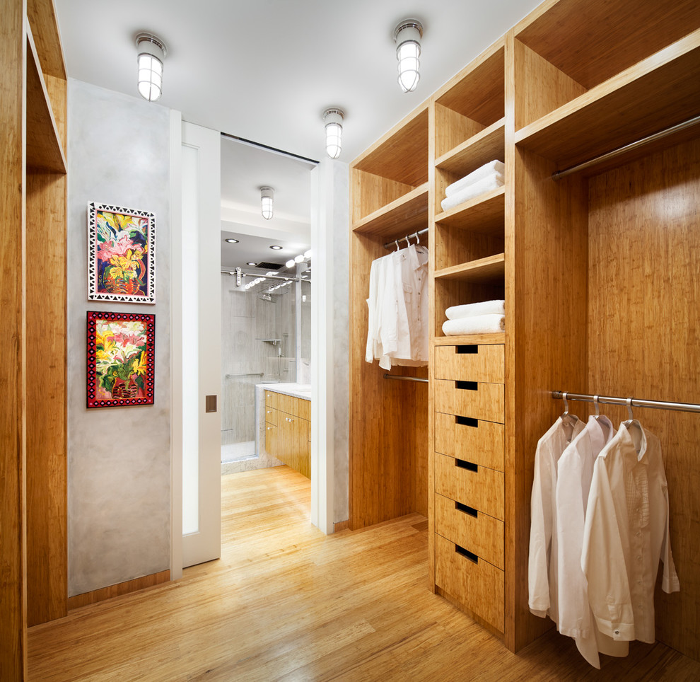 Small trendy gender-neutral bamboo floor walk-in closet photo in New York with open cabinets and light wood cabinets