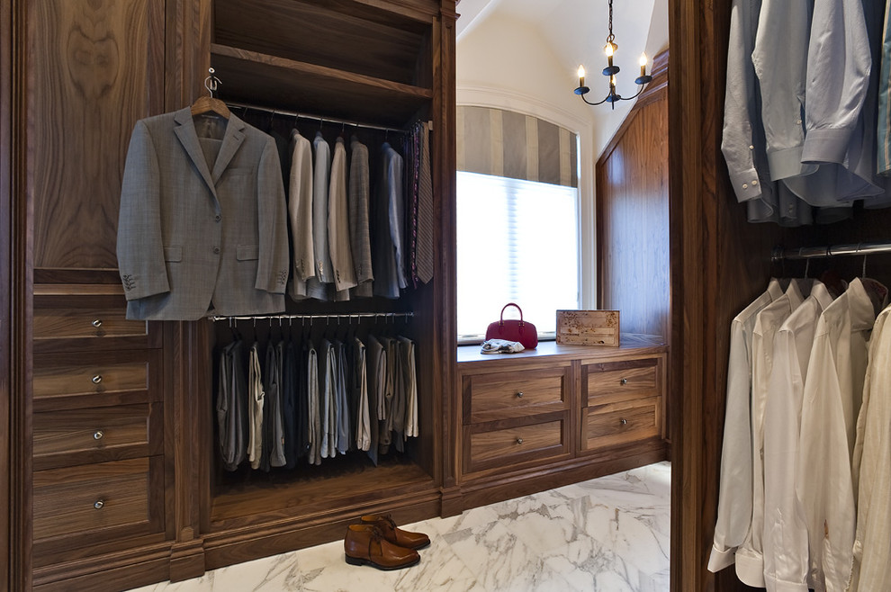 Inspiration for a large timeless men's marble floor walk-in closet remodel in Toronto with dark wood cabinets and recessed-panel cabinets