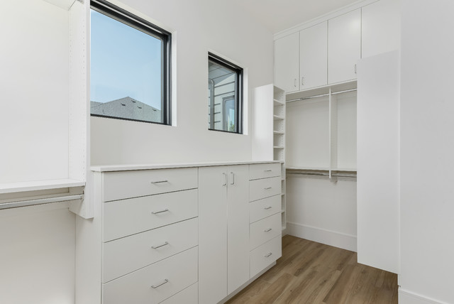 Walk-in closet - large contemporary gender-neutral porcelain floor and beige floor walk-in closet idea in Salt Lake City with flat-panel cabinets and white cabinets