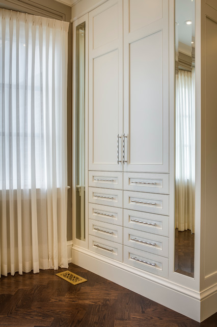 Dressing room - mid-sized modern gender-neutral medium tone wood floor dressing room idea in Toronto with white cabinets and recessed-panel cabinets