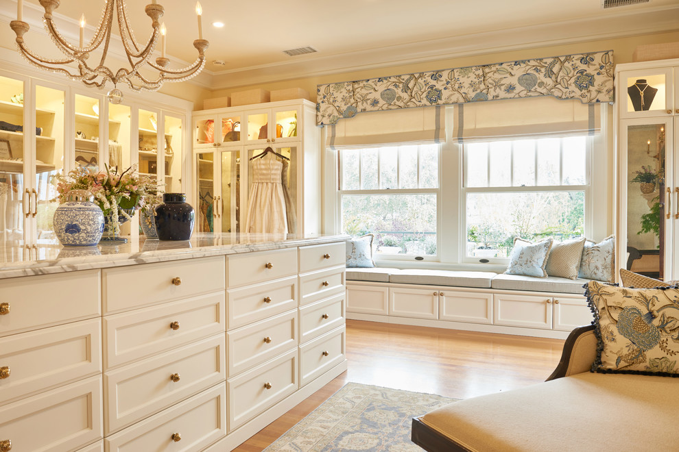 Example of a huge classic women's light wood floor and brown floor dressing room design in Los Angeles with glass-front cabinets and white cabinets