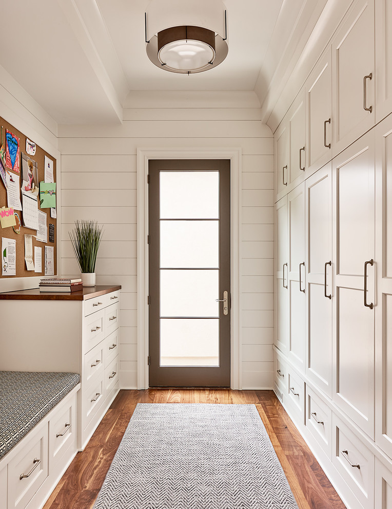 Transitional gender-neutral medium tone wood floor walk-in closet photo in Charlotte with shaker cabinets and white cabinets