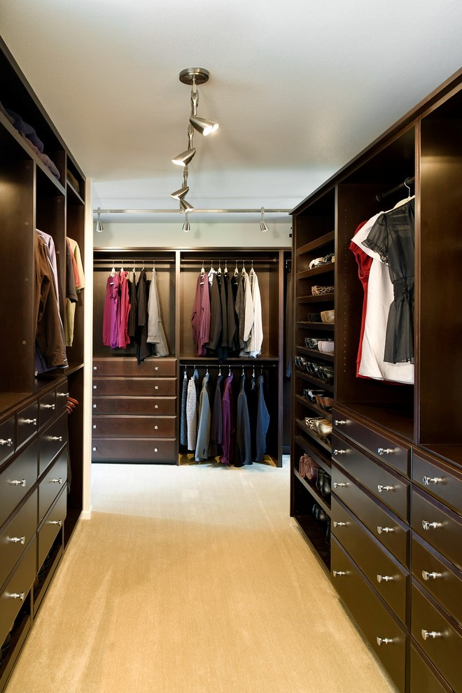 Walk-in closet - large traditional gender-neutral carpeted walk-in closet idea in Portland with raised-panel cabinets and dark wood cabinets