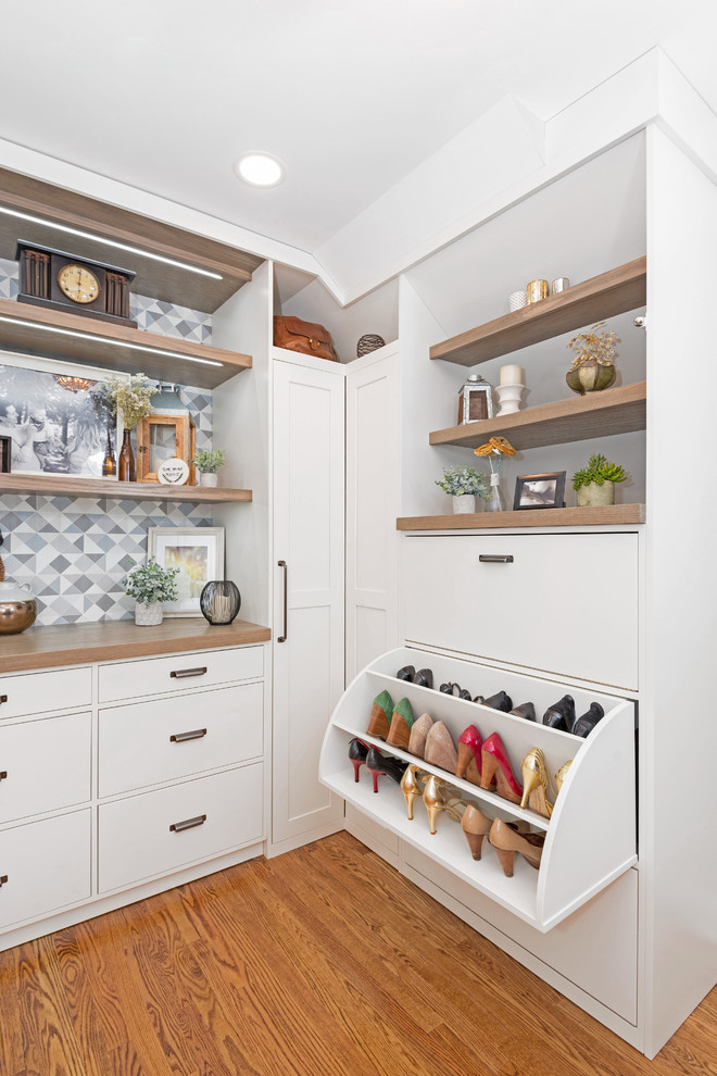 Example of a large transitional gender-neutral medium tone wood floor and brown floor dressing room design in Other with white cabinets and shaker cabinets