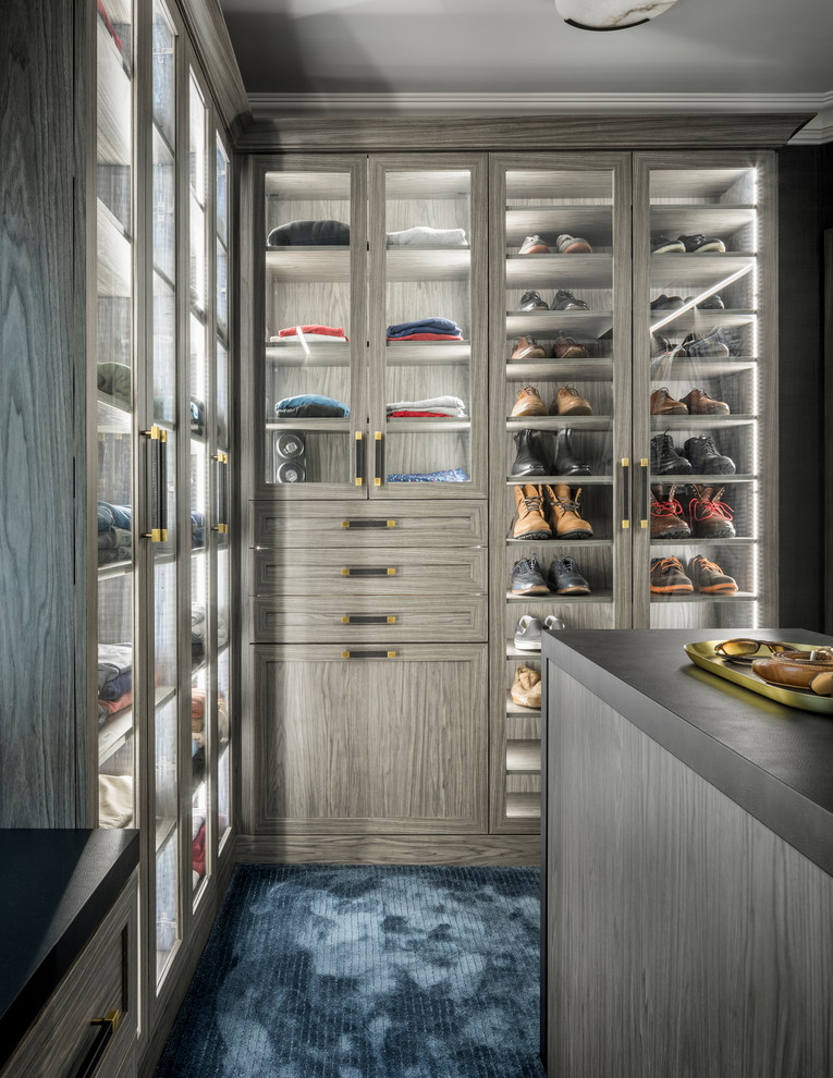 Example of a large trendy men's carpeted and blue floor walk-in closet design in New York with gray cabinets and glass-front cabinets
