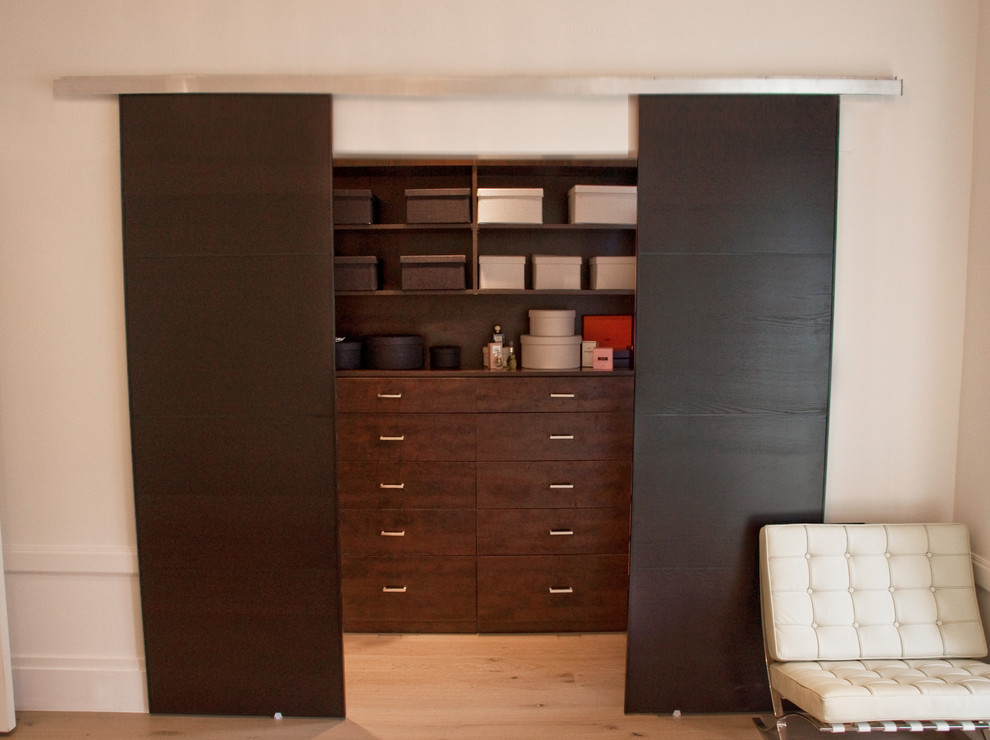 Inspiration for a mid-sized modern gender-neutral light wood floor walk-in closet remodel in San Francisco with flat-panel cabinets and dark wood cabinets