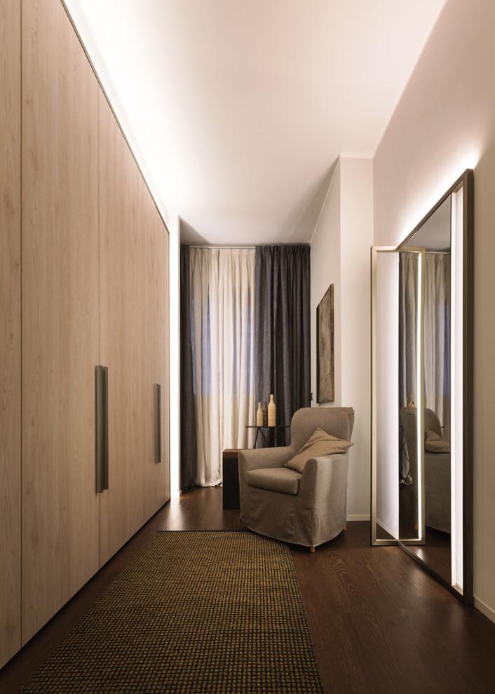 Neutrales Modernes Ankleidezimmer mit hellen Holzschränken, Ankleidebereich, flächenbündigen Schrankfronten und dunklem Holzboden in Mailand