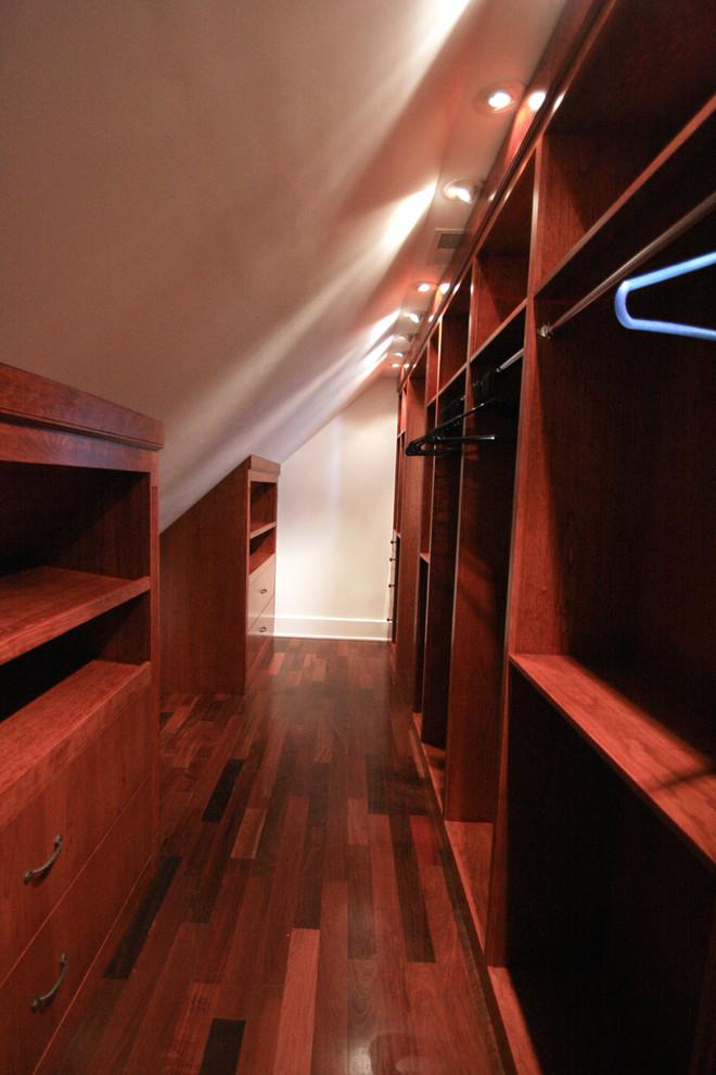 Example of a large classic gender-neutral medium tone wood floor walk-in closet design in DC Metro with medium tone wood cabinets
