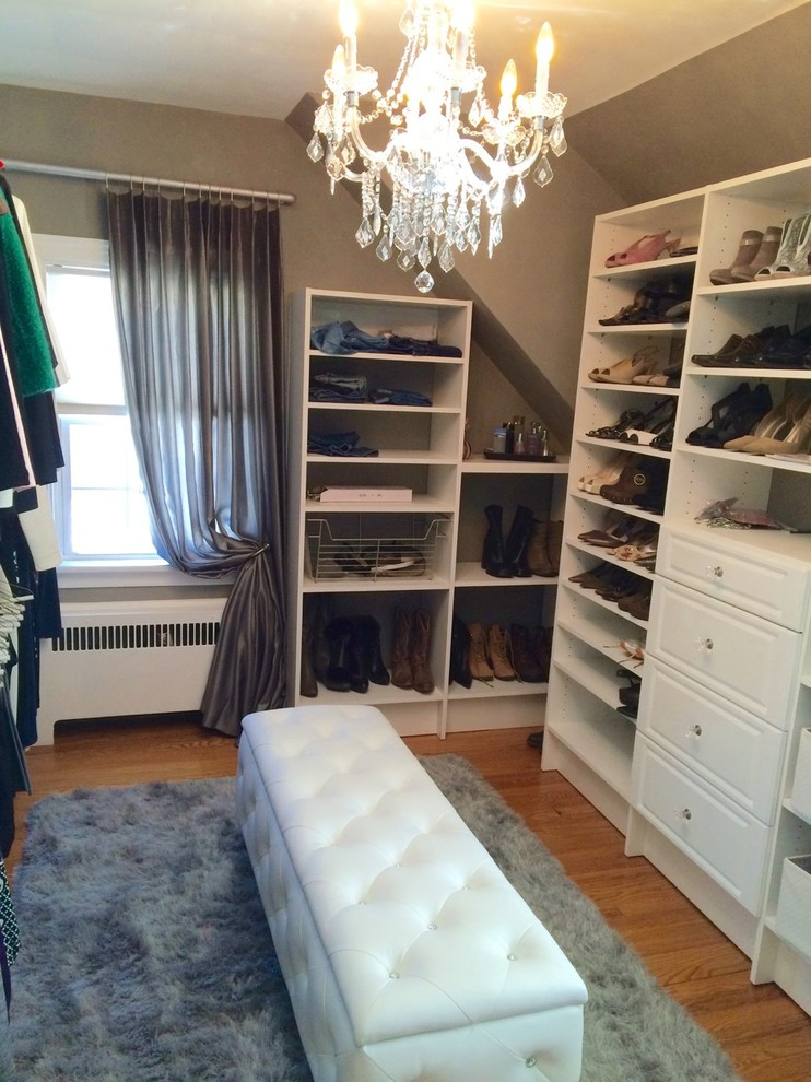 Inspiration for a mid-sized transitional women's light wood floor walk-in closet remodel in New York with raised-panel cabinets and white cabinets