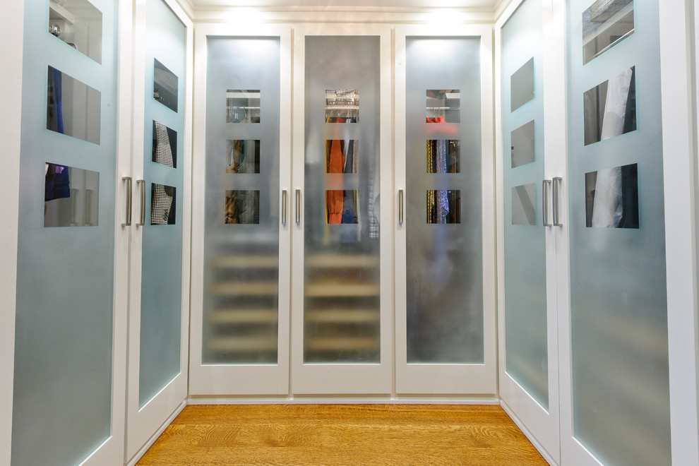 Inspiration for a timeless light wood floor walk-in closet remodel in Philadelphia with glass-front cabinets and white cabinets
