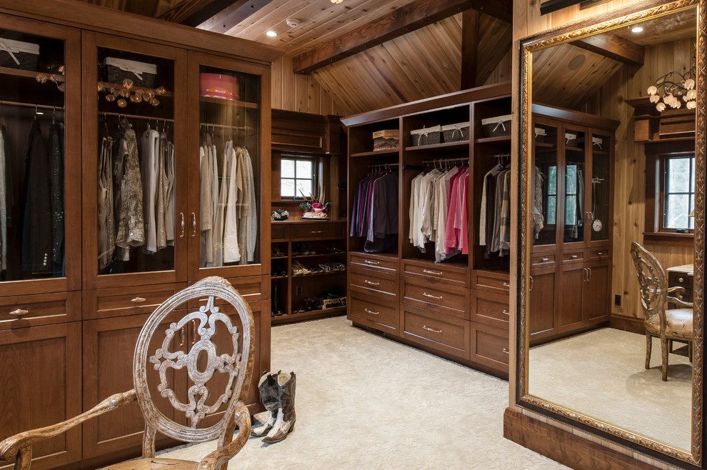 Mid-sized elegant gender-neutral carpeted and beige floor dressing room photo in Other with recessed-panel cabinets and dark wood cabinets