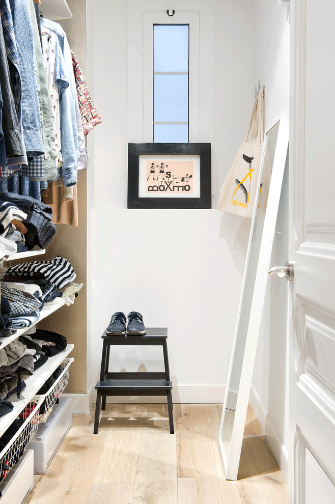 Inspiration for a mid-sized scandinavian gender-neutral light wood floor and beige floor walk-in closet remodel in Barcelona with open cabinets and white cabinets