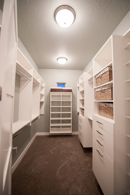Example of a mid-sized trendy gender-neutral carpeted and brown floor walk-in closet design in Salt Lake City with flat-panel cabinets and white cabinets
