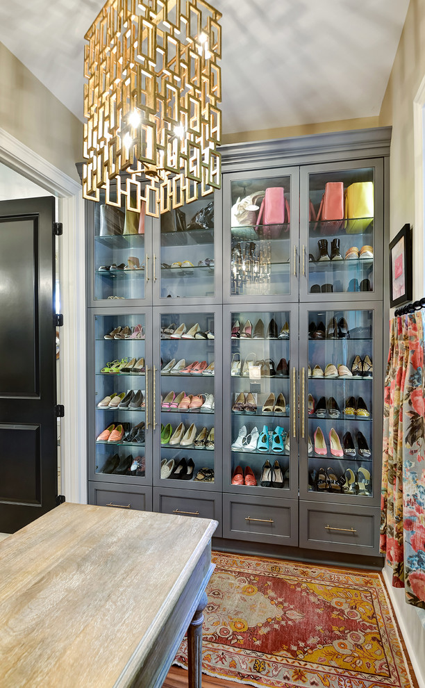 Transitional women's walk-in closet photo in Charleston with glass-front cabinets and gray cabinets