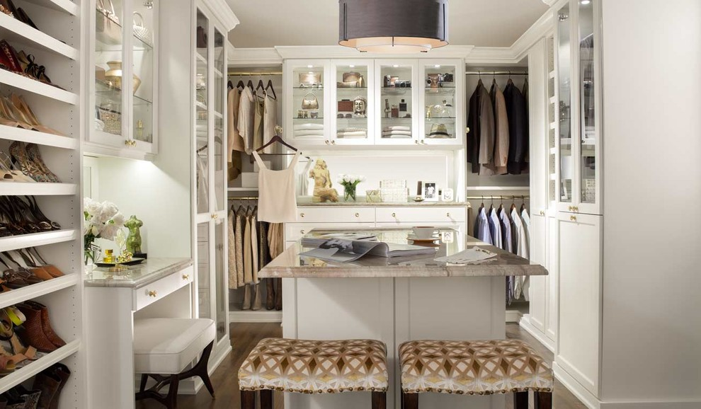 Large elegant gender-neutral dark wood floor dressing room photo in New York with glass-front cabinets and white cabinets