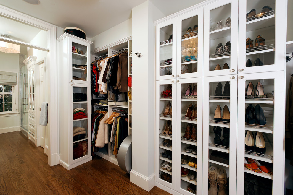Example of a classic medium tone wood floor walk-in closet design in DC Metro with white cabinets
