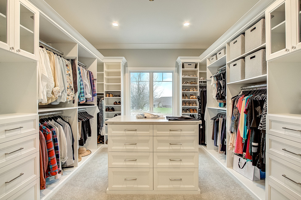 Inspiration for a traditional gender neutral dressing room in Milwaukee with recessed-panel cabinets, white cabinets, carpet and beige floors.
