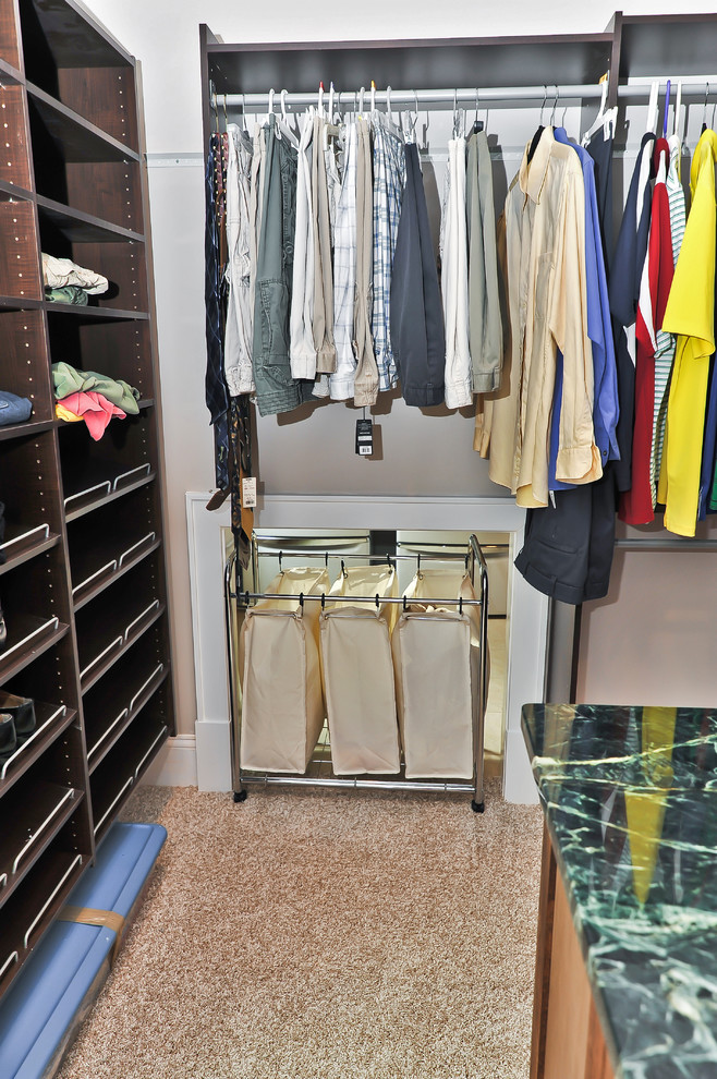 Elegant men's walk-in closet photo in DC Metro with open cabinets and dark wood cabinets