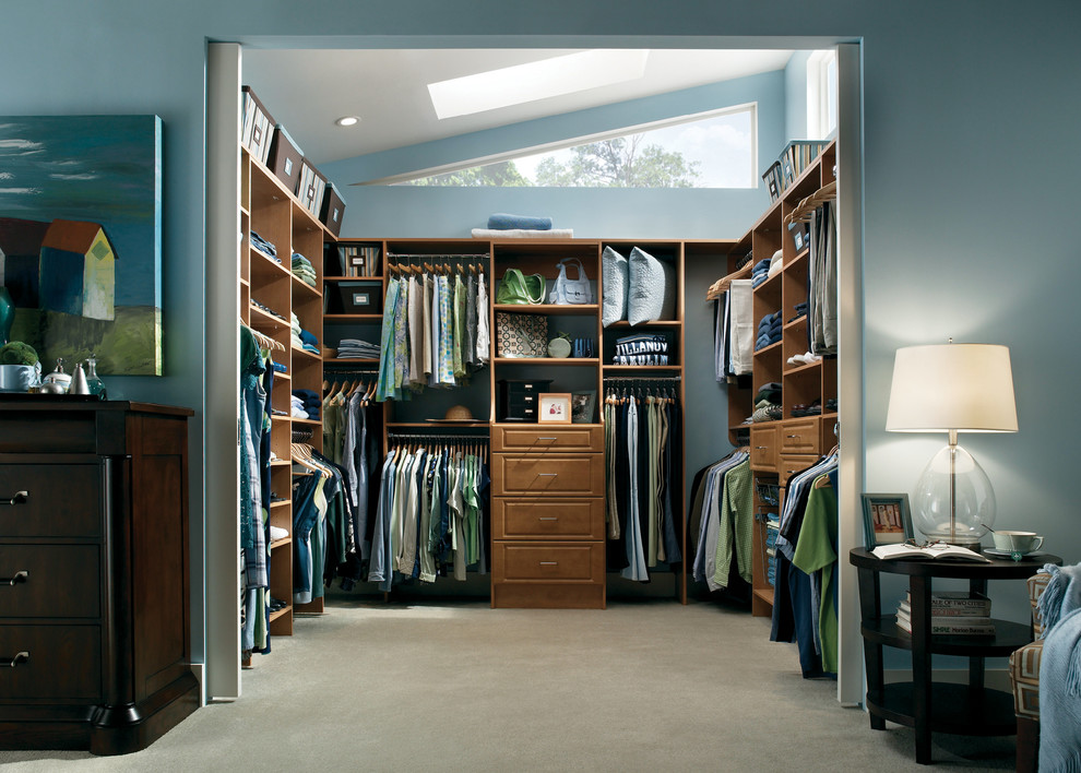 Example of a mid-sized transitional gender-neutral carpeted walk-in closet design in Boston with raised-panel cabinets and medium tone wood cabinets