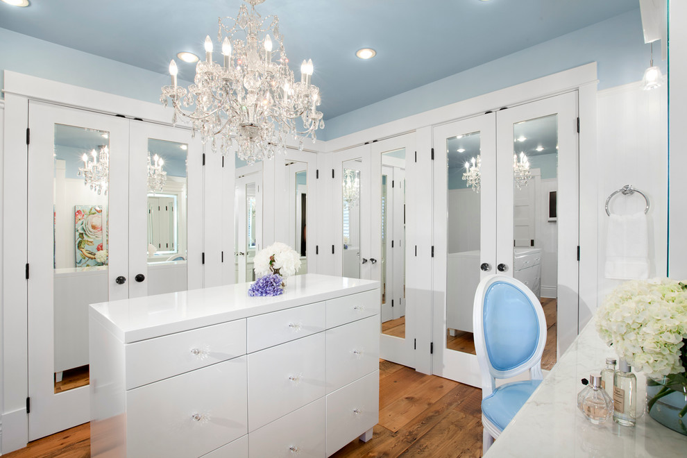 Immagine di uno spazio per vestirsi classico con ante bianche e pavimento in legno massello medio