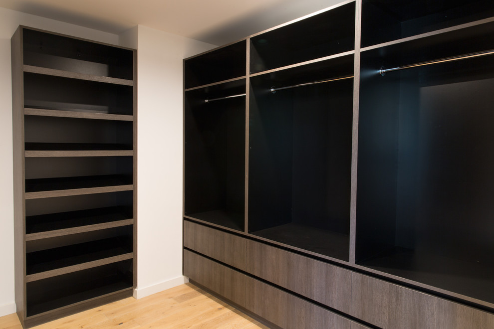 Large minimalist gender-neutral light wood floor walk-in closet photo in Los Angeles with flat-panel cabinets and dark wood cabinets