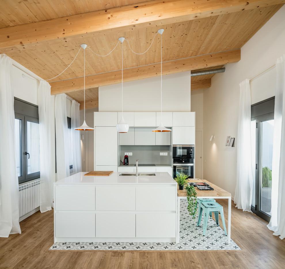 Ejemplo de cocina de galera, escandinava, abierta, con fregadero bajoencimera, armarios con paneles lisos, puertas de armario blancas, salpicadero verde, electrodomésticos negros, una isla, suelo multicolor y encimeras blancas