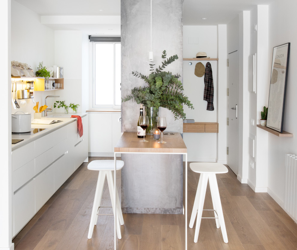 Inspiration for a small scandinavian single-wall medium tone wood floor eat-in kitchen remodel in Barcelona with an undermount sink, flat-panel cabinets, white cabinets, a peninsula and white backsplash