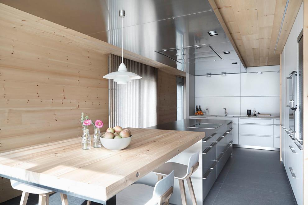 Foto de cocina lineal, escandinava, grande, abierta, con armarios con paneles lisos, puertas de armario blancas, electrodomésticos de acero inoxidable, suelo de baldosas de cerámica y una isla