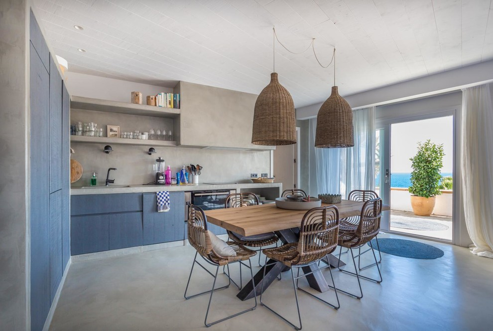 Eat-in kitchen - mid-sized mediterranean l-shaped concrete floor and gray floor eat-in kitchen idea in Other with blue cabinets, concrete countertops, gray backsplash, no island and flat-panel cabinets