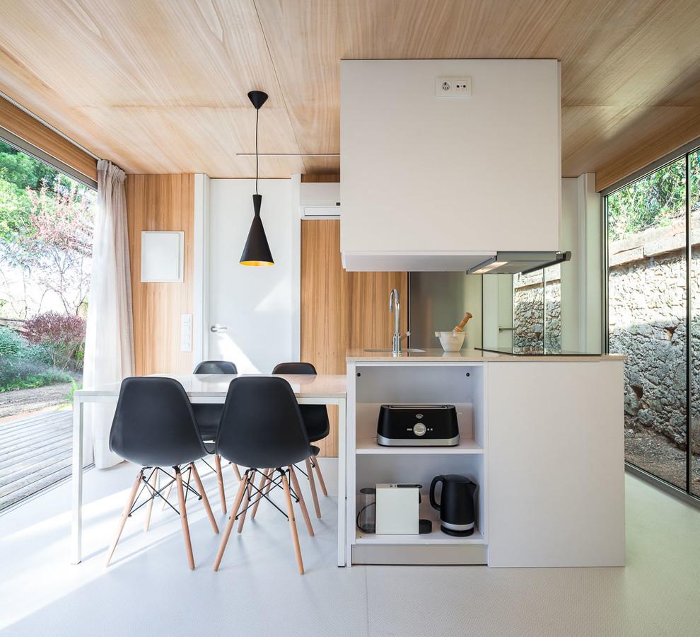 Diseño de cocina actual, abierta, con puertas de armario blancas y suelo blanco