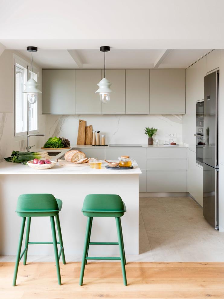 Kitchen - mid-sized scandinavian u-shaped beige floor kitchen idea in Barcelona with flat-panel cabinets, gray cabinets, white backsplash, a peninsula, a single-bowl sink, stone slab backsplash, stainless steel appliances and white countertops