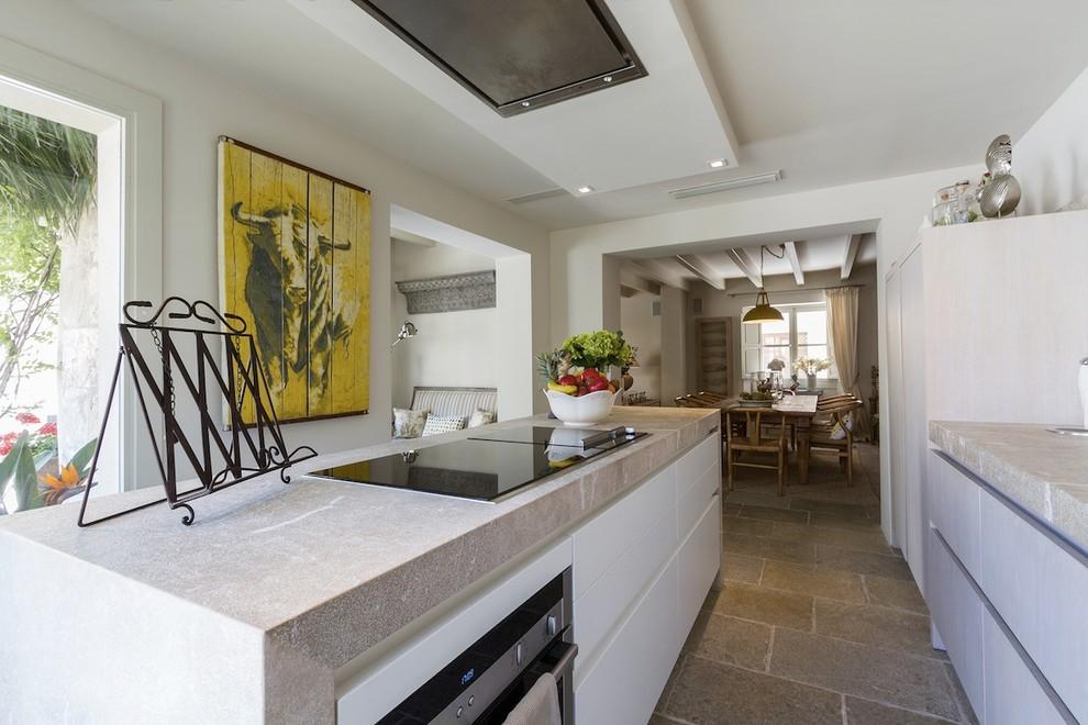 Ispirazione per una grande cucina mediterranea con ante lisce, ante bianche, top in pietra calcarea, elettrodomestici in acciaio inossidabile e pavimento in pietra calcarea