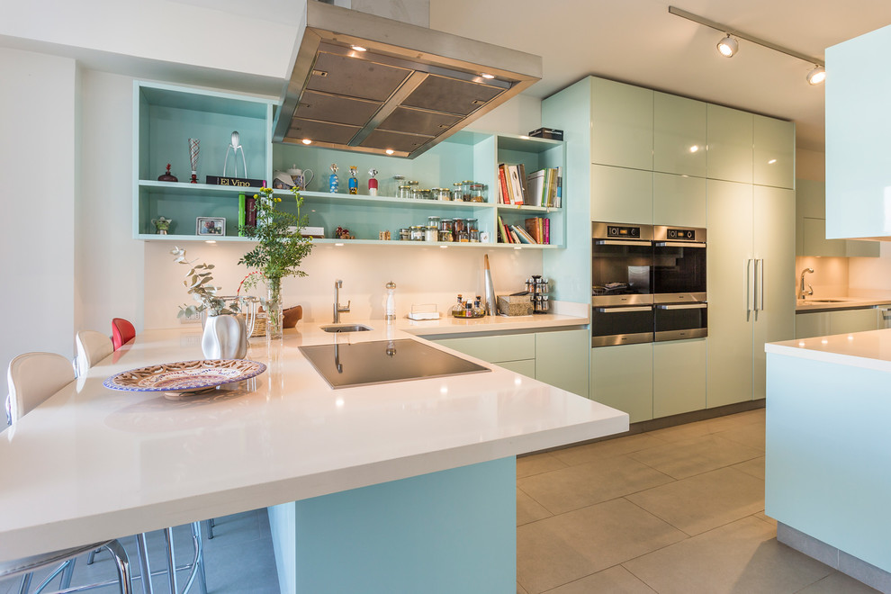 Inspiration for a huge modern l-shaped gray floor kitchen remodel in Madrid with an undermount sink, flat-panel cabinets, blue cabinets, white backsplash, stainless steel appliances, a peninsula and white countertops