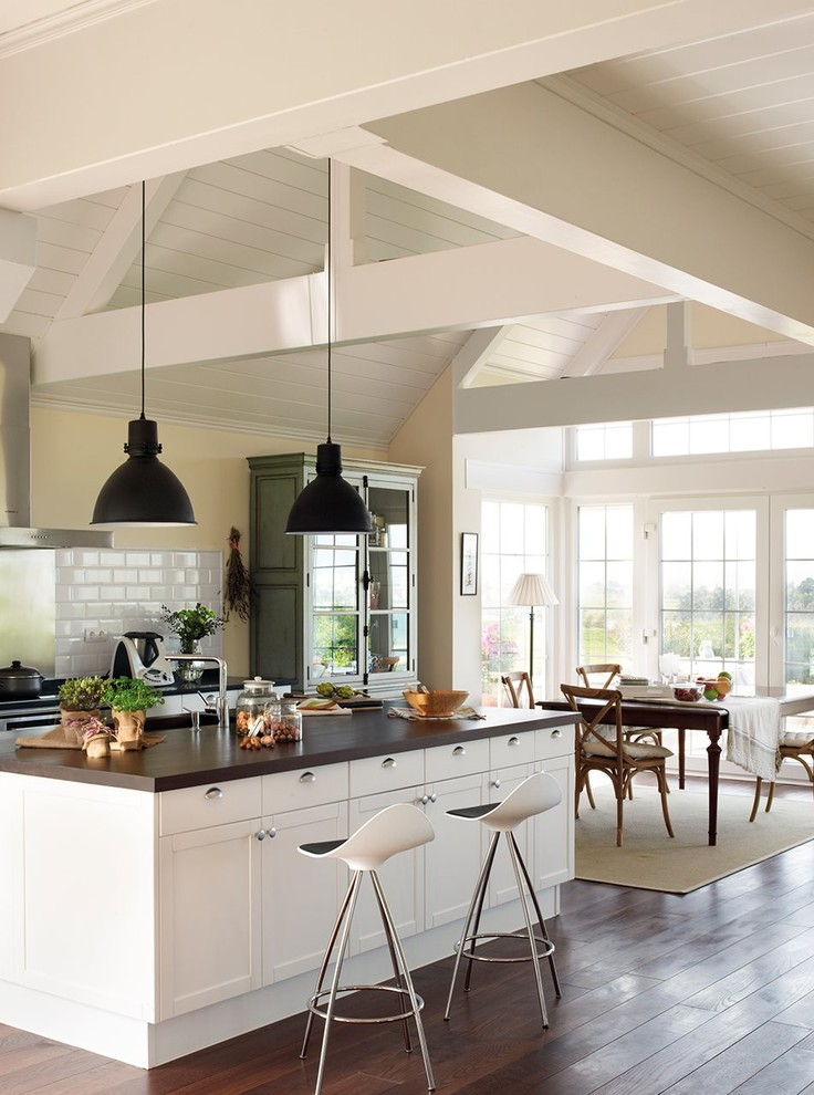 Inspiration for a mid-sized timeless single-wall dark wood floor open concept kitchen remodel in Other with a single-bowl sink, beaded inset cabinets, white cabinets, wood countertops, white backsplash, porcelain backsplash, white appliances and an island