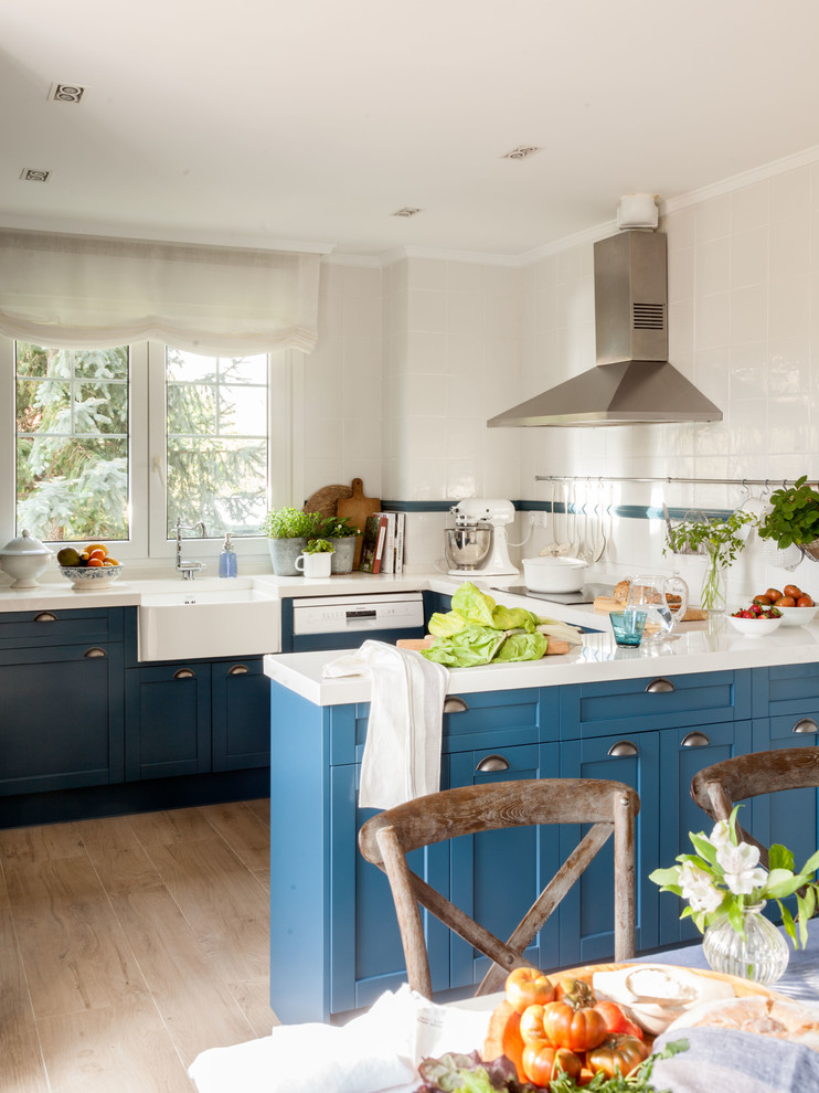 Eat-in kitchen - transitional u-shaped light wood floor and brown floor eat-in kitchen idea in Bilbao with a farmhouse sink, shaker cabinets, blue cabinets, white backsplash, a peninsula and white countertops