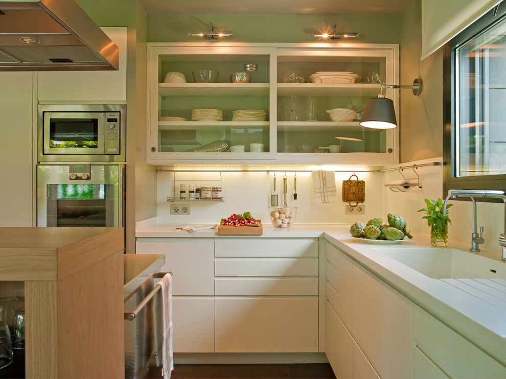 Enclosed kitchen - mid-sized contemporary l-shaped enclosed kitchen idea in Barcelona with white cabinets, white backsplash, stainless steel appliances, an integrated sink, glass-front cabinets, solid surface countertops and an island