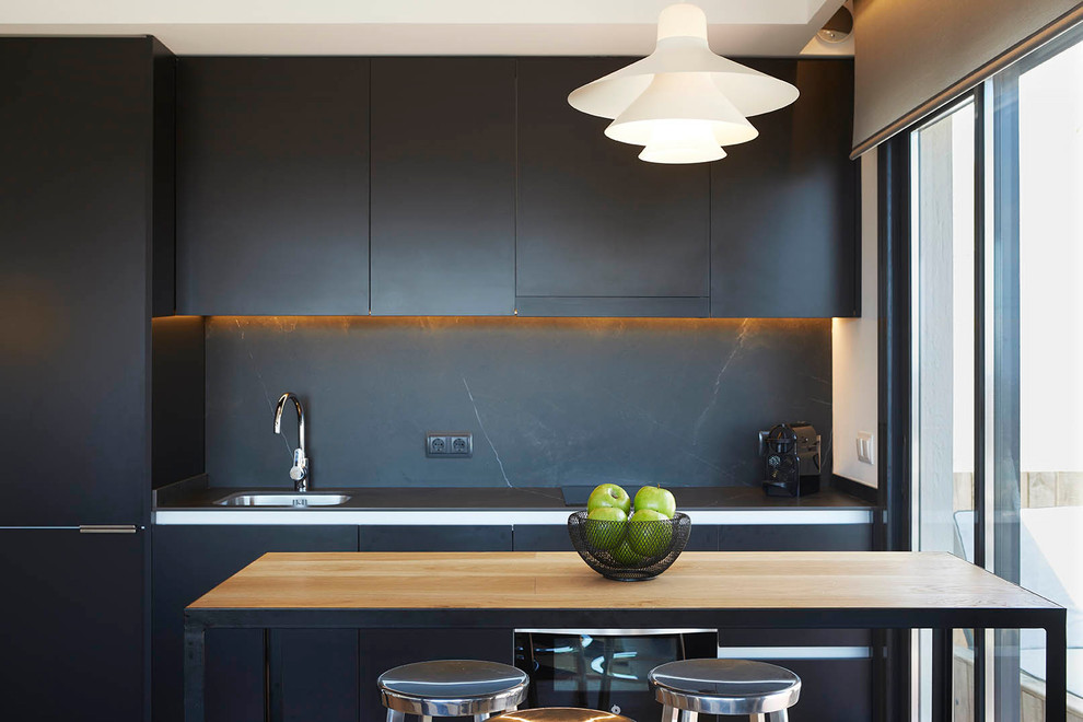 Inspiration for a contemporary single-wall kitchen remodel in Barcelona with a drop-in sink, flat-panel cabinets, black cabinets, black backsplash and an island