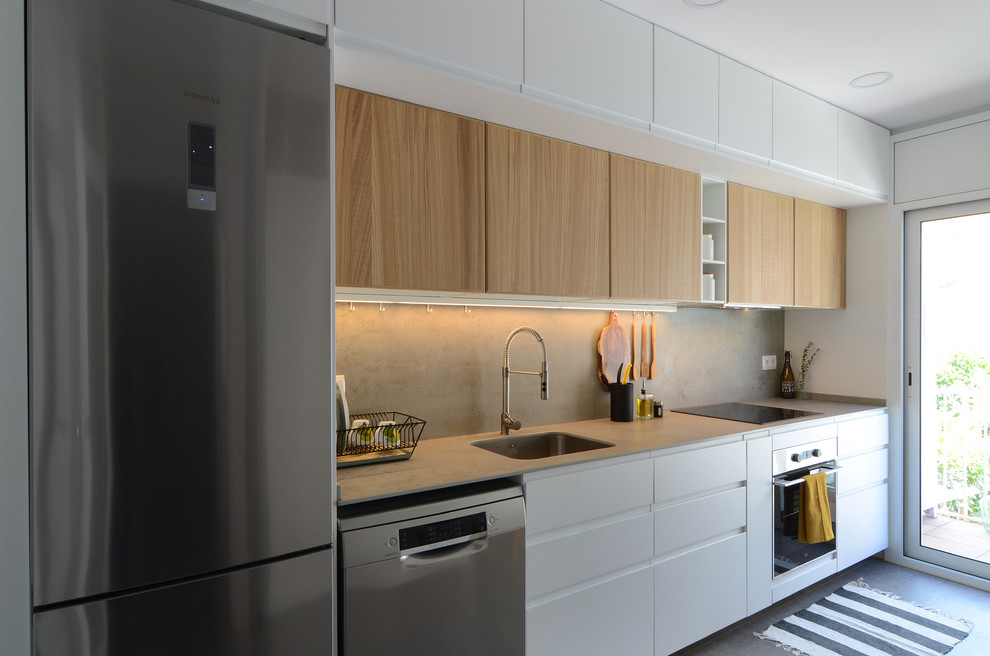 Example of a mid-sized trendy single-wall gray floor kitchen design in Barcelona with an undermount sink, white cabinets, gray backsplash, stainless steel appliances, gray countertops, flat-panel cabinets and no island