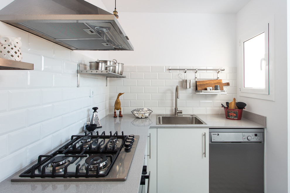 Small urban l-shaped enclosed kitchen photo in Barcelona with a drop-in sink, flat-panel cabinets, white cabinets, solid surface countertops, white backsplash, subway tile backsplash, stainless steel appliances, no island and gray countertops