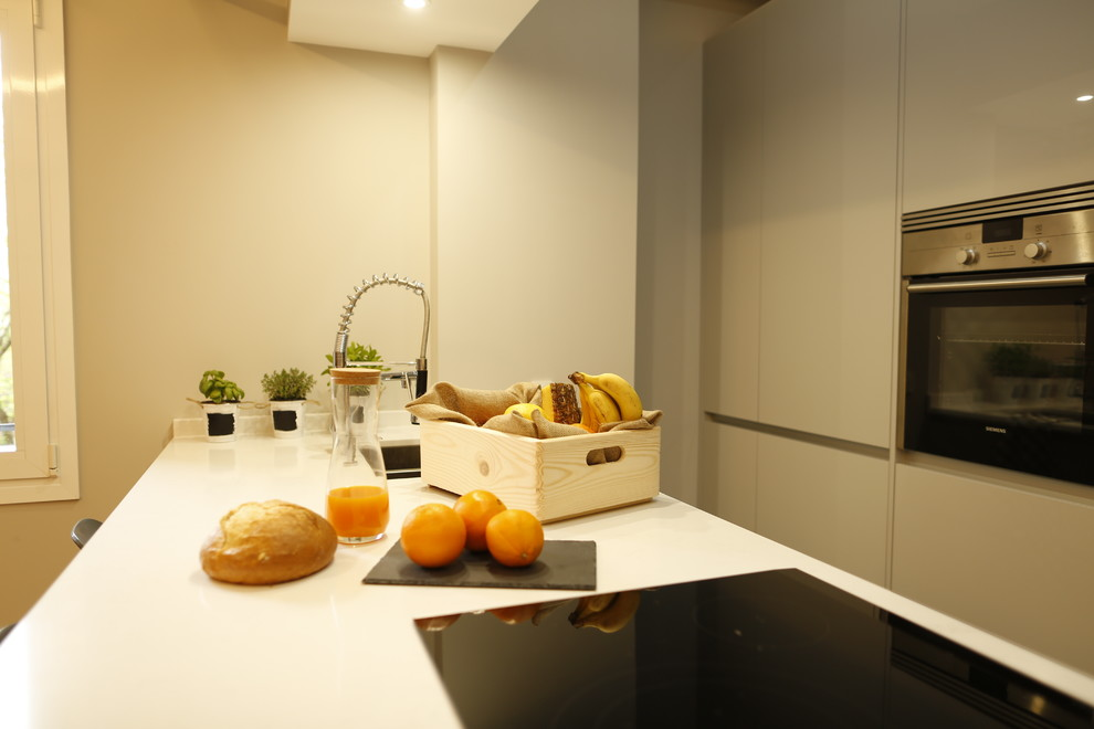 Example of a large minimalist single-wall ceramic tile and multicolored floor kitchen design in Madrid with a double-bowl sink, gray cabinets, metallic backsplash, stainless steel appliances, an island and white countertops